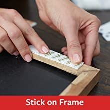 hands applying command picture hanging strips to the back of a frame