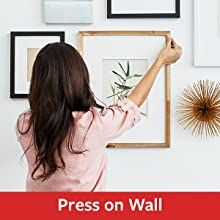 Woman pressing a frame to a wall with Command Picture hanging strips